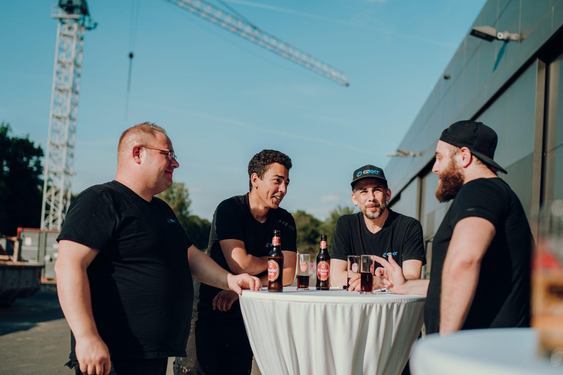 Klimatechniker trinken ein Bier am Stehtisch
