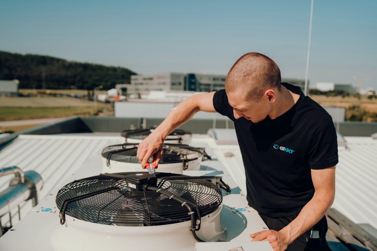 G-KKT Mitarbeiter checkt mit Werkzeug die Lüftungstechnik auf dem Dach