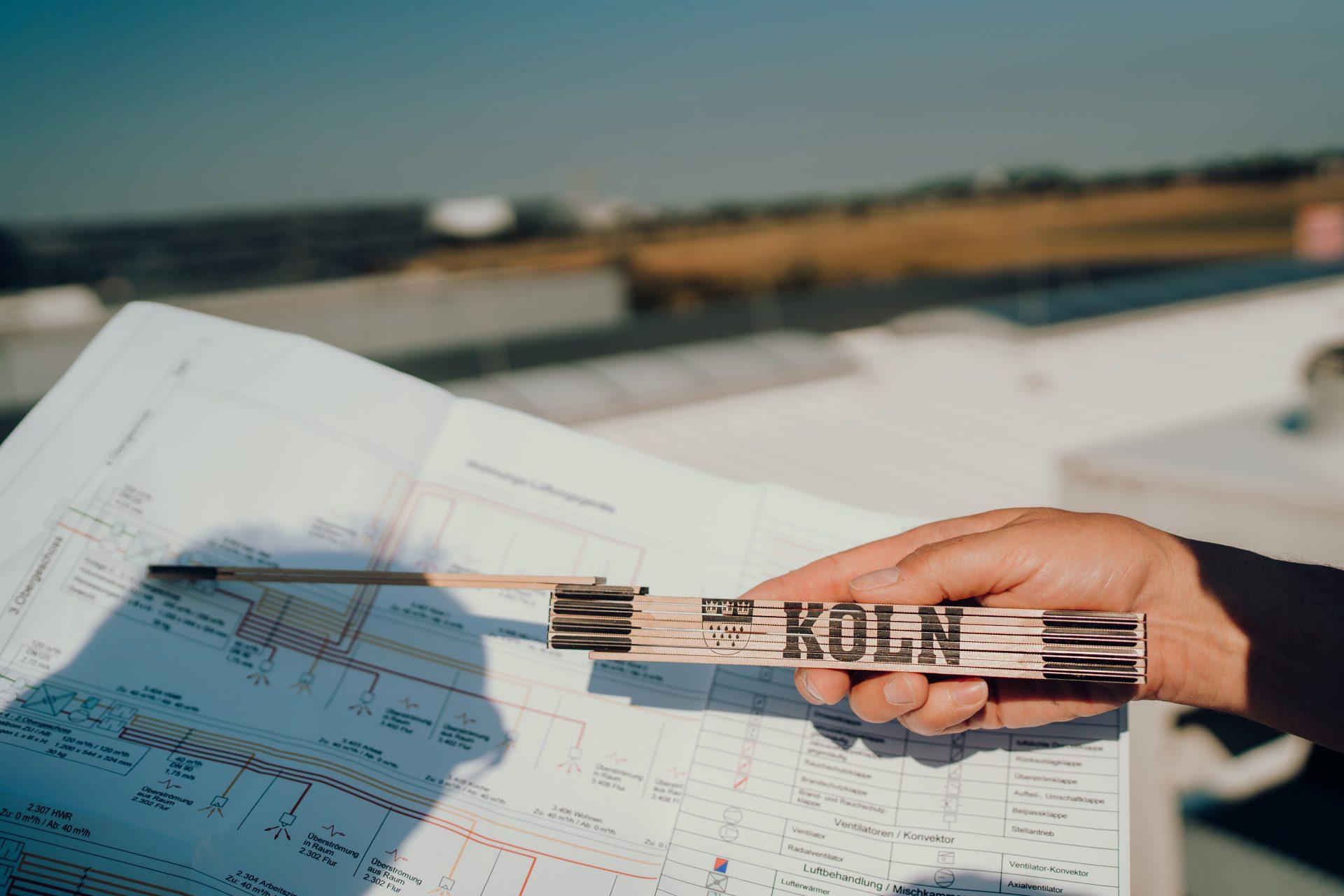 Zollstock mit Köln Aufschrift zeigt auf Bauplan